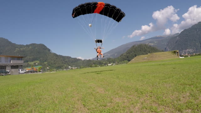Tandem skydivers landing on field