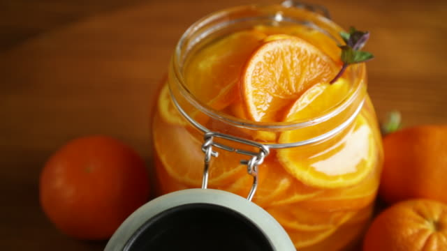 tangerine jam in a glass jar on a wooden table video