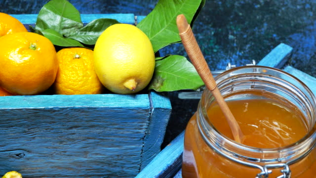 Tangerine jelly Tangerine jelly or marmalade with lemon, ginger and cinnamon on blue tray. Fresh tangerine and lemon fruit in blue box. Dolly shot jar stock videos & royalty-free footage