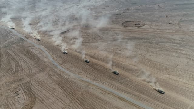 tank convoy Epic aerial view of military tanks convoy riding fast in the desert sand dunes leaving behind massive trail of dust, war operation tank shot. Convoy force of 6 heavy armed tanks driving in formation towards combat attack in army tank exercise army stock videos & royalty-free footage