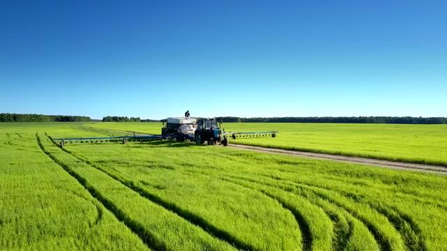 vidéos et rushes de le camion de réservoir et le pulvérisateur de tracteur pour des produits chimiques se tiennent sur la route parmi des champs - équipement agricole