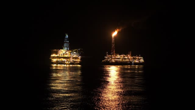 FPSO tanker vessel near Oil platform Rig at night. Offshore oil and gas industry video