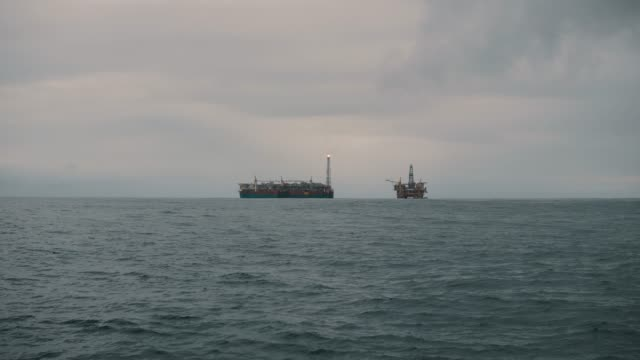 FPSO tanker vessel near Oil Rig platform. Offshore oil and gas industry video