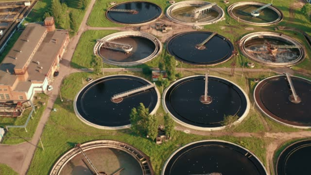 Tanks or pools for sedimentation and filtration, primary and secondary wastewater treatment at wastewater treatment plant, aerial view from drone video