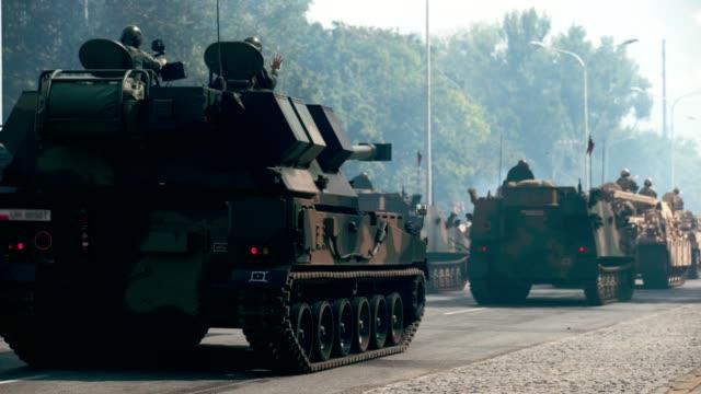Tanks riding along city streets