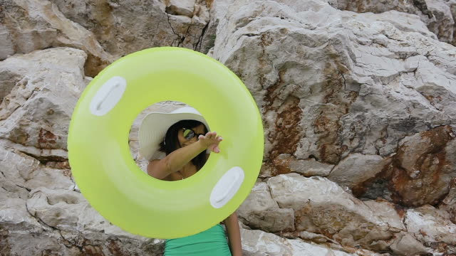 en solbränd flicka i en baddräkt och en hatt är gör en rolig twist av en uppblåsbar flytcirkel på handen och tittar i kameran på rock bakgrund. ung kvinna med gul uppblåsbar flottör - inflatable ring bildbanksvideor och videomaterial från bakom kulisserna