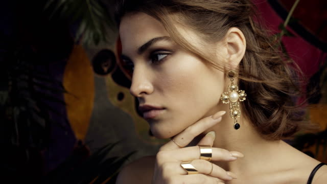 Tanned girl with large gold earrings among tropical leaves.