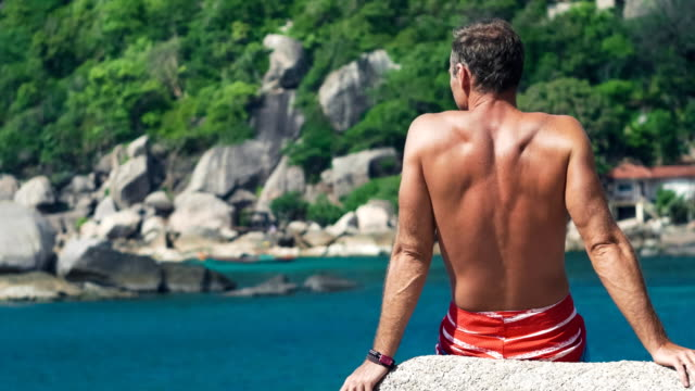 Tanned travler men relax on stone in front of Tanote Bay on Koh Tao Island, Thailand, Asia video