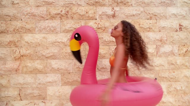 Tanned woman spinning with inflatable flamingo and blowing bubble gum video