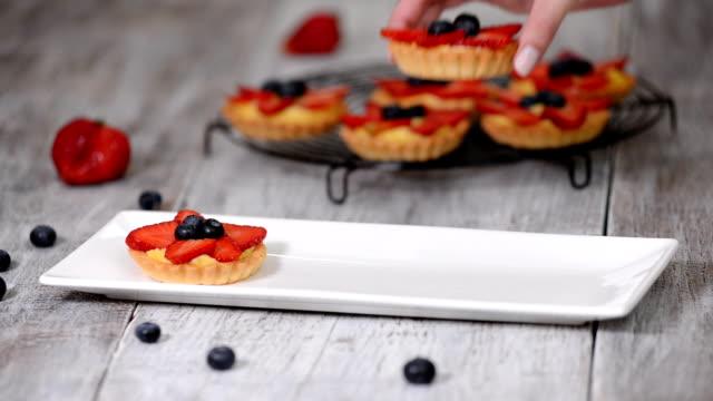 Tartlets with custard, strawberries and blueberries. Tasty dessert.