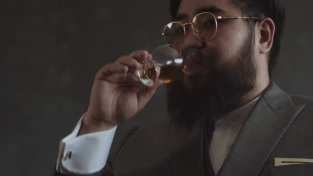 tasting expensive alcoholic beverage, man drinking cognac - brandy video stock e b–roll