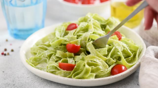 vídeos de stock e filmes b-roll de tasting green spinach pasta - meat plate