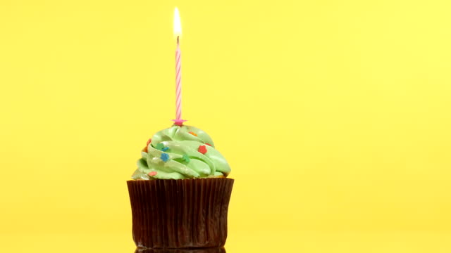 tasty birthday cupcake with candle, on yellow background video