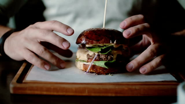vídeos y material grabado en eventos de stock de sabrosa hamburguesa es grande en una bandeja de madera. un hombre toma sus manos y come, pruebe el sabor - hamburguesa