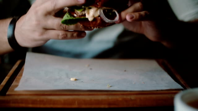 Tasty burger is great on a wooden tray. A man takes his hands and eats, try the taste video