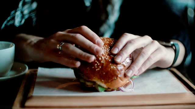Tasty burger is great on a wooden tray. A woman takes his hands and was going to eat video