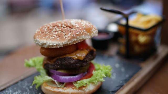 tasty cheeseburger served on appetizer plate at outdoor gastro pub - cheeseburger filmów i materiałów b-roll