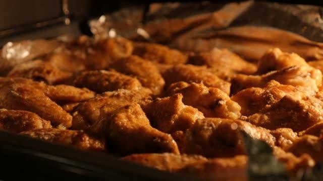 vidéos et rushes de viande de poulet savoureux cuite et prête à être servis footage panoramique de close-up 4k 2160p 30fps ultrahd - ailes de poulet buffalo dans le four après la cuisson lente pan 3840 x 2160 uhd vidéo - four