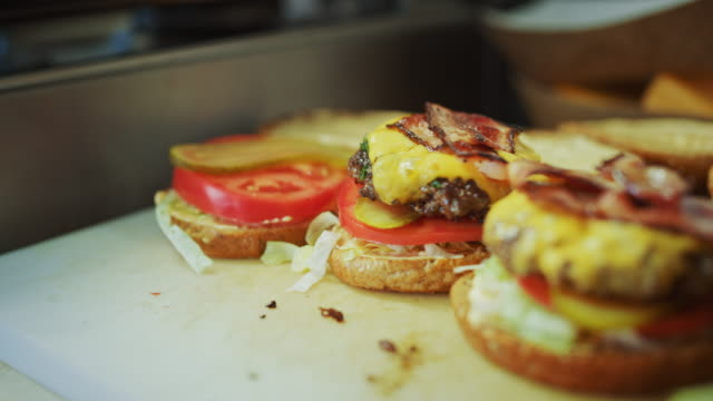 Tasty Close Up Footage of a Cook Preparing Burgers. Food Chef is Adding a Flaming Hot Grounded Beef Patty with Melted Cheese to a Burger Bun with Salad, Tomatos and Cucumberg.