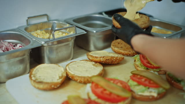Tasty Close Up Footage of a Cook Preparing Burgers. Food Chef is Adding Souce on top of Buns with Sesame Seeds. Fresh Gourmet Burgers with Beef Patty, Salad, Tomatos and Cucumberg are Being Prepared.