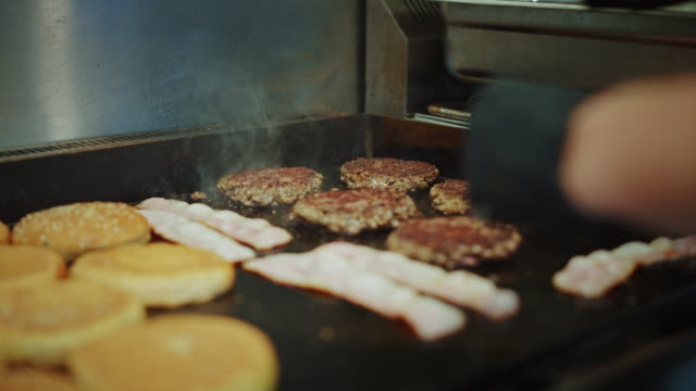 Tasty Close Up Footage of a Meat Patties Prepared on a Griller. Fresh Ground Beef is Grilled on a Hot Electric Grill. Cook is Turning a Patty for Burger from Minced Meat and Seasoning it with Salt.