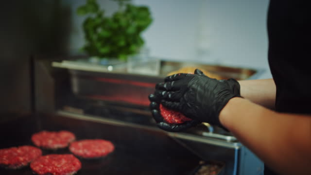 Tasty Close Up Footage of a Meat Patty Being Prepared on a Griller. Fresh Ground Beef is Being Put on a Hot Gas or Electric Grill. Cook is Forming a Patty for Burger from Fresh Minced Meat.