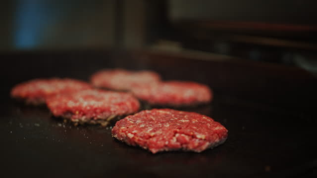 Tasty Close Up Footage of a Meat Patty Being Prepared on a Griller. Fresh Ground Beef is Grilled on a Hot Gas or Electric Grill. Cook is Seasoning a Patty for Burger from Fresh Minced Meat with Salt.