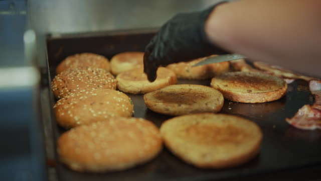 Tasty Footage of a Cook Flipping Burger Buns with Sesame Seeds on a Hot Gas or Electric Griller. Fresh Gourmet Burgers are Being Prepared.