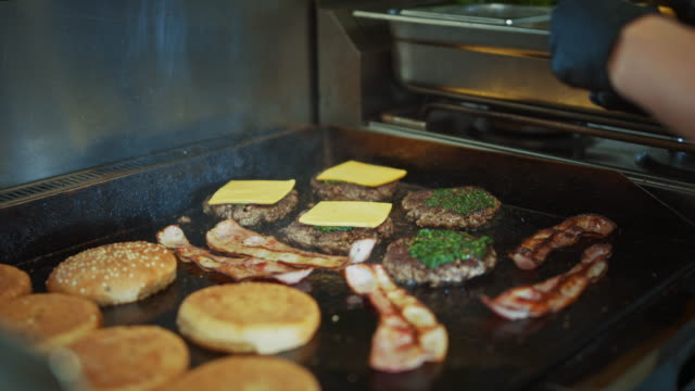 Tasty Footage of a Meat Patties Being Prepared. Fresh Ground Beef is Grilled on a Hot Gas or Electric Grill. Cook is Adding Cheese Slices on Top of Minced Meat.