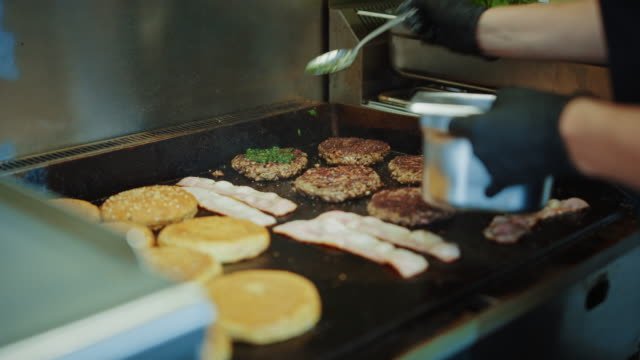 Tasty Footage of a Meat Patty Being Prepared on a Griller. Fresh Ground Beef is Grilled on a Hot Gas or Electric Grill. Cook is Adding Home Made Green Pesto Sauce to Patty for Burger from Minced Meat.