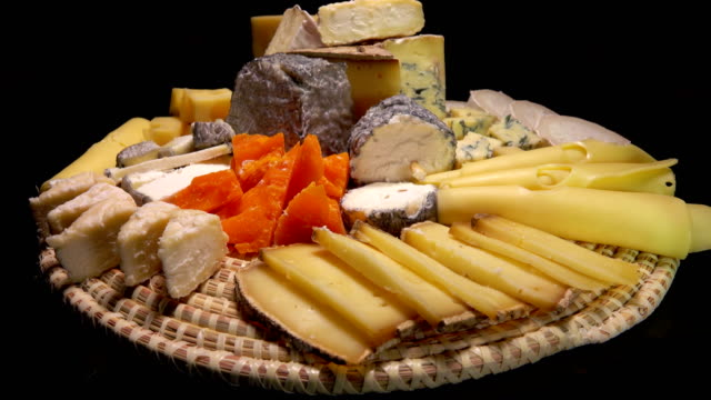 Tasty French cheeses on a plate on a black background Circular movement of the camera around of pieces tasty French cheeses on a plate on a black background cheese stock videos & royalty-free footage