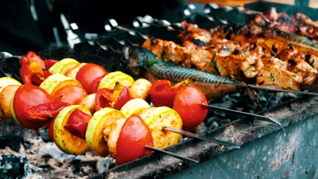 Tasty fresh meat strung on a skewer is fried on brazier. Shish kebab from pork and vegetables video