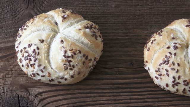 Tasty freshly baked kaiser rolls with seeds on wooden board Tasty freshly baked kaiser rolls with seeds on wooden board sesame stock videos & royalty-free footage