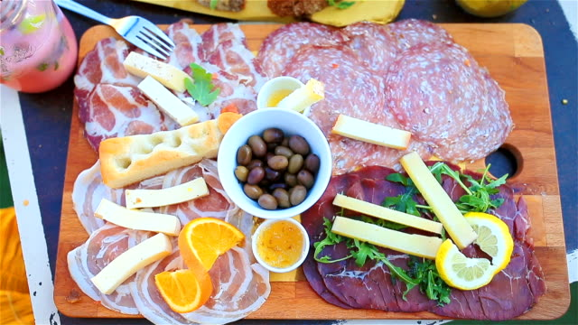 Tasty italian food. Fresh bruschettes, cheeses and meat on the board in outdoor cafe with amazing view in Manarola, Italy video
