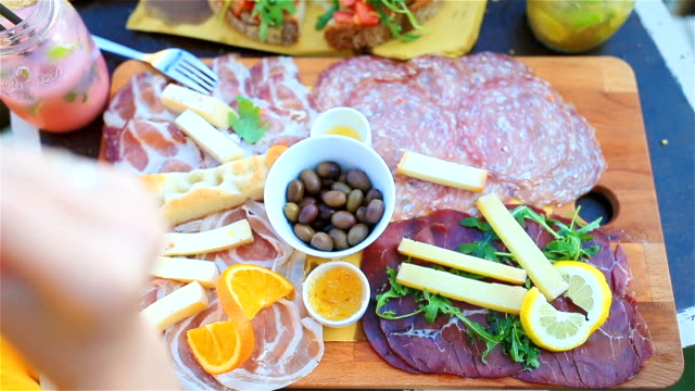 Tasty italian food. Fresh bruschettes, cheeses and meat on the board in outdoor cafe with amazing view in Manarola, Italy Tasty italian snack. Fresh bruschettes, cheeses and meat on the board in outdoor cafe with amazing view in Manarola aperitif stock videos & royalty-free footage