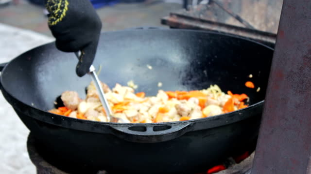 Tasty, juicy meat is fried with vegetables in huge bowl and mixed with a spoon at a street food festival video