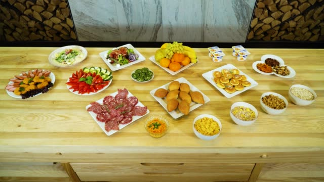 tasty meals variety appearing and disappearing on big wooden table - comparsa video stock e b–roll