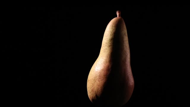 tasty pear rotating on black background with dramatic light - video
