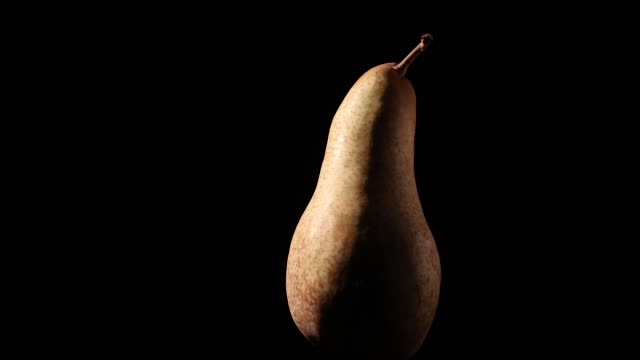 tasty pear rotating on black background with dramatic light video