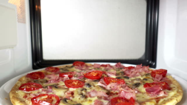 Tasty pizza topped with tomato mushroom and ham heating in microwave oven video