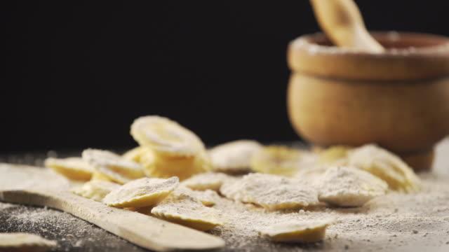 vídeos de stock e filmes b-roll de tasty raw ravioli with flour and basil - ravioli