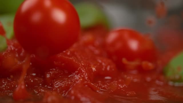 vídeos de stock e filmes b-roll de macro: tasty tomato sauce with basil splashes as cherry tomatoes fall into it. - sauce tomatoes