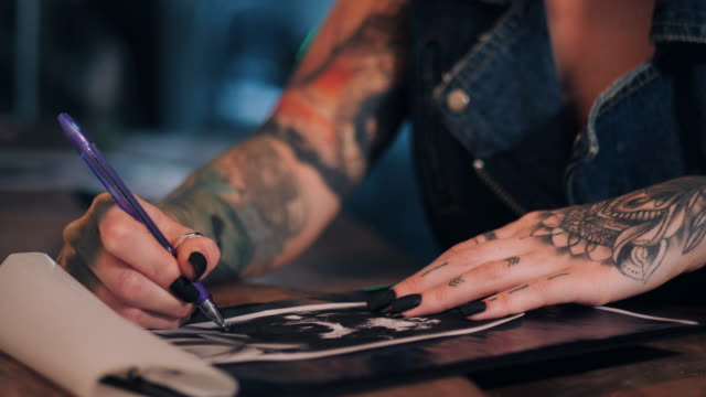 Tattoo artist drawing illustration of skull inside ink studio. Woman with black nails and rings at work. New fashion lifestyle artistic trends concept . Warm cinematic filter Tattoo artist drawing illustration of skull inside ink studio. Woman with black nails and rings at work. New fashion lifestyle artistic trends concept . Warm cinematic filter. tattoo stock videos & royalty-free footage