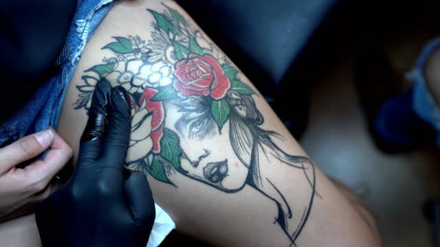 tattoo artist making tattoo on customer's leg - tatuaż filmów i materiałów b-roll