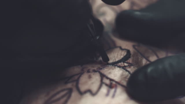 Tattoo master making tattoo on customer's leg Tattoo master making tattoo on customer's leg tattoo stock videos & royalty-free footage