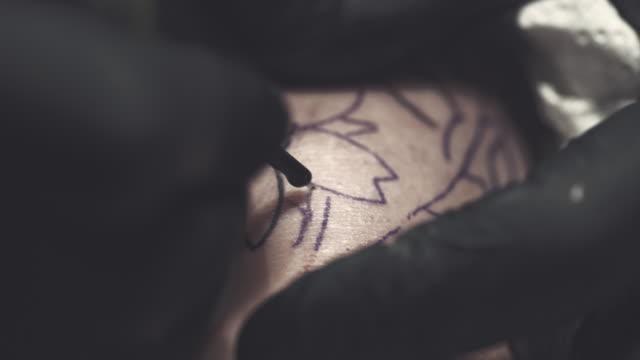 tattoo master making tattoo on customer's leg - tatuaż filmów i materiałów b-roll