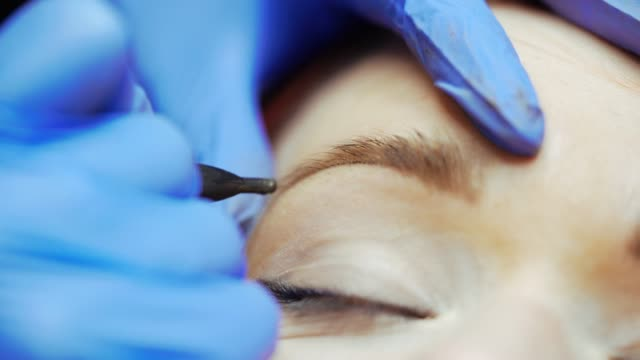 vídeos de stock e filmes b-roll de tattoo specialist in gloves is drawing eyebrows with a thin needle for a woman in a beauty salon. - sobrancelha