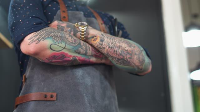 tätowierter friseur in seinem friseurladen - tätowierung stock-videos und b-roll-filmmaterial