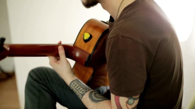 en tatuerad kille som spelar gitarr. - chain studio bildbanksvideor och videomaterial från bakom kulisserna