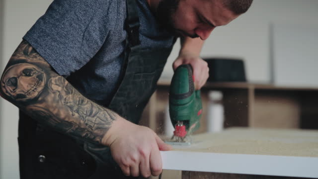 Tattooed Handy Man Drilling Plank Tattooed Handy Man Drilling Plank And Fixing New Wooden Table renovation stock videos & royalty-free footage